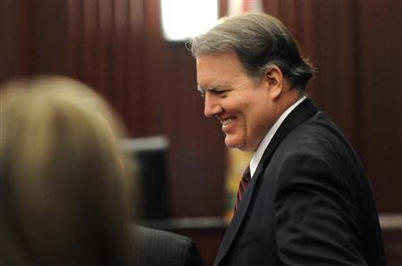 A smiling Michael Dunn talks with his lawyer Cory Strolla after the jury began their deliberations in Jacksonville, Florida February 15, 2014. REUTERS/Bob Mack/Florida Times-Union/Pool