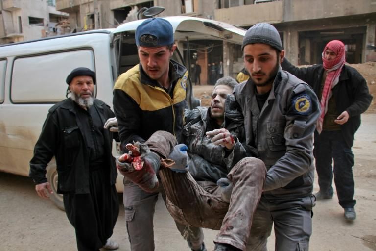 Civil Defence volunteers, known as the White Helmets, carry a wounded man into a makeshift hospital in the rebel-held town of Douma, following air strikes by regime forces on the besieged Eastern Ghouta region on February 20, 2018
