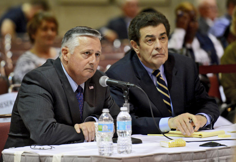 FILE- In this Feb. 17, 2016 file photo, Retired Rear Admiral Philip H. Greene, Jr, President and CEO of TOTE Services, Inc., left, answer questions from the board at a hearing investigating the sinking of the El Faro ship in Jacksonville, Fla. The story of the cargo ship El Faro's final hours was reconstructed using thousands of pages of public documents, hours of testimony before the U.S. Coast Guard's investigative board and interviews with crew family members and maritime experts. (Bob Mack/The Florida Times-Union via AP, File)