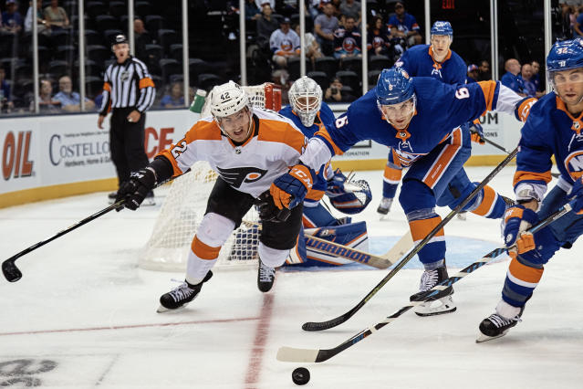 New York Islanders' Ryan Pulock (6) and Stephen Gionta, right, fights for the puck with Philadelphia Flyers' Cole Bardreau, left, during the first period of a preseason NHL hockey game in New York, Sunday, Sept. 16, 2018. (AP Photo/Andres Kudacki)