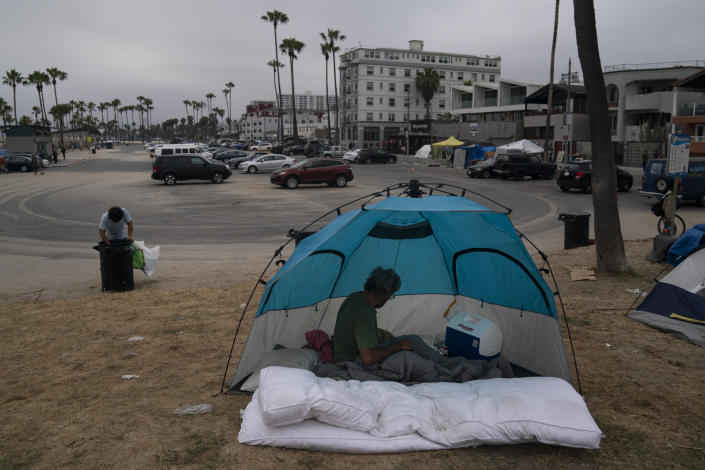 Jose Formoso, who said he moved from Malibu, Calif., after his RV burned down, sits in his tent near the boardwalk in the Venice neighborhood of Los Angeles, Tuesday, June 29, 2021. (AP Photo/Jae C. Hong)
