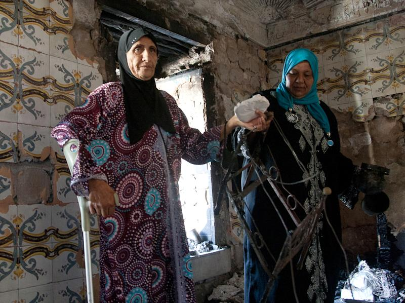 Women hold stones after masked individuals attacked and set fire to the popular 500-year-old shrine of Manouba, west of Tunis, early Tuesday, Oct. 16, 2012. The shrine, which serves as a refuge for poor women, is also a place of symbolic worship for many Tunisians who visit the shrine bringing along food, money and candles. (AP Photo/Amine Landoulsi)