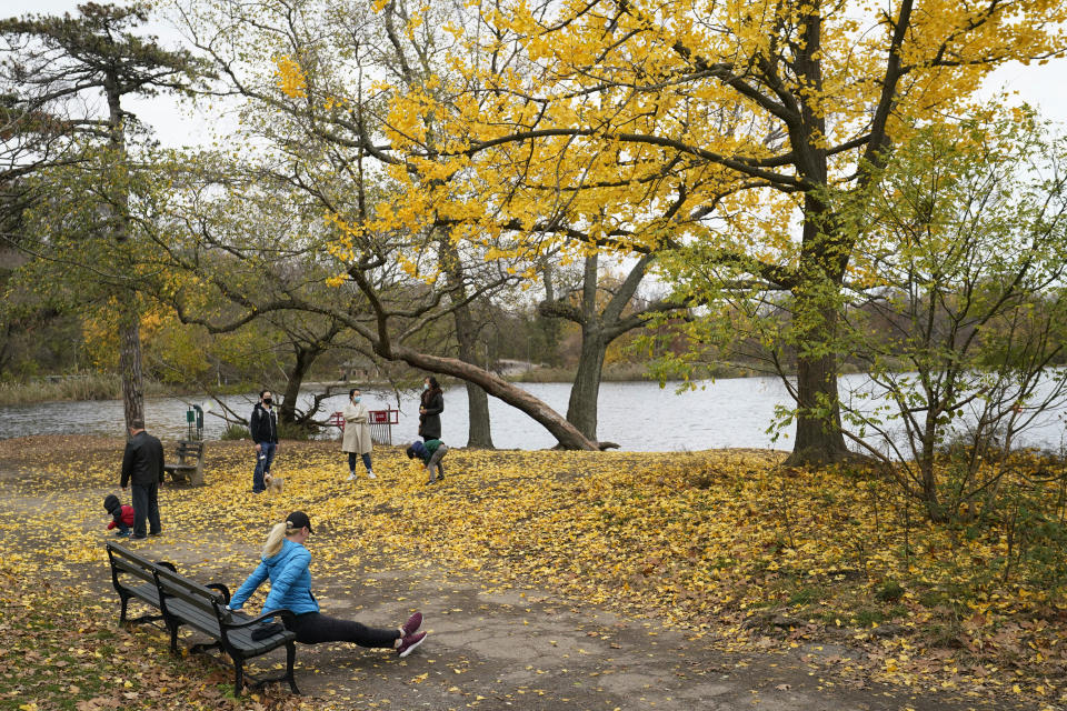 A woman exercises using a park bench as children play with leaves from a Ginkgo tree adjacent to the lake, Sunday, Nov. 15, 2020, in Prospect Park in the Brooklyn borough of New York. (AP Photo/Kathy Willens)