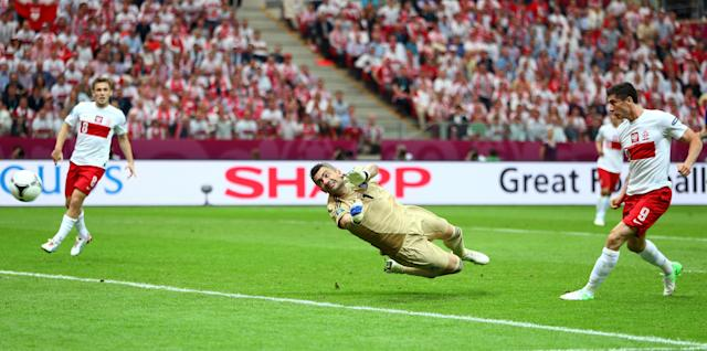 WARSAW, POLAND - JUNE 08: Robert Lewandowski of Poland scores the opening goal past Konstantinos Chalkias of Greece during the UEFA EURO 2012 Group A match between Poland and Greece at National Stadium on June 8, 2012 in Warsaw, Poland. (Photo by Michael Steele/Getty Images)