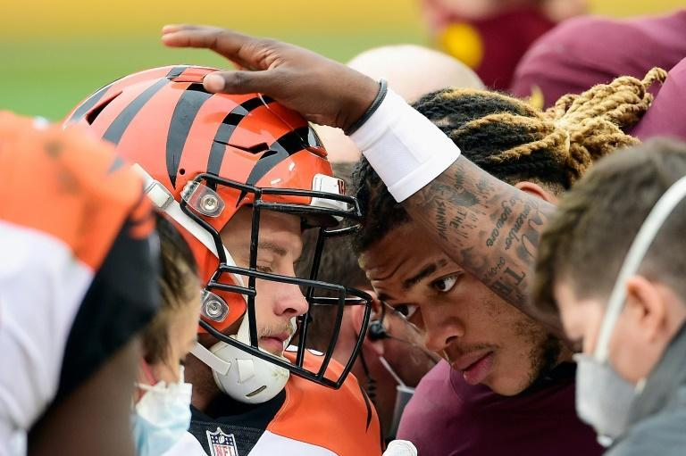 Players offer encouragement to Cincinnati quarterback Joe Burrow after a knee injury forced him out of the Bengals' NFL game against Washington