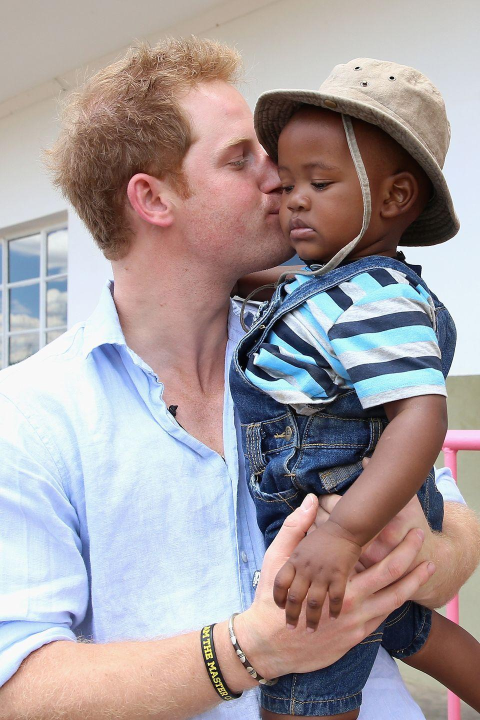 <p>Prince Harry kisses a young child at the Thuso Centre for children in Bute-Bute, Lesotho.</p>