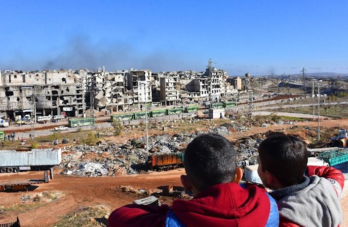 Syrian children watch as buses depart during an evacuation operation of rebel fighters and civilians from rebel-held neighbourhoods of Aleppo on December 15, 2016 (AFP Photo/George Ourfalian)
