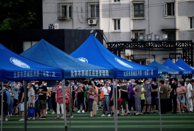 People who visited or live near Xinfadi Market, linked to a new cluster of coronavirus infections in Beijing, queue for a swab test at Guang'an Sport Center on June 14, 2020 (AFP Photo/NOEL CELIS)