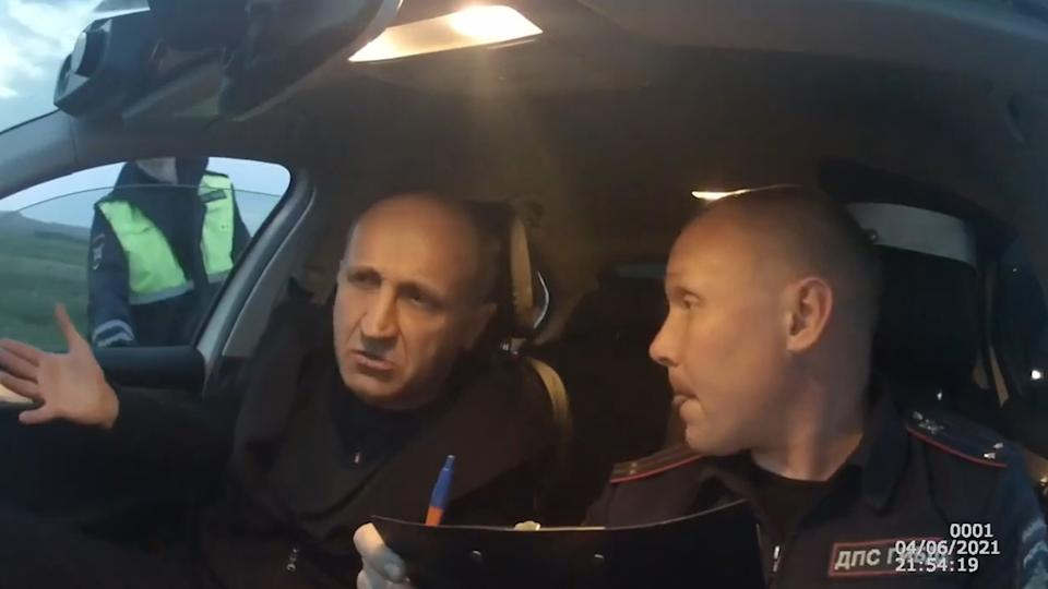 A suspected drunk driver speaks with a police officer in the Irkutsk region in Russia on June 4, 2021.