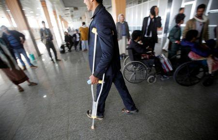 A wounded Houthi fighter walks at Sanaa airport during his evacuation from Yemen