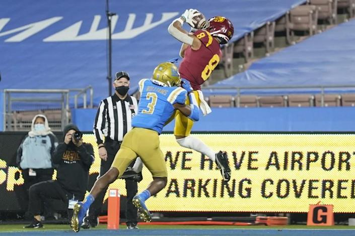 USC's Amon-ra St. Brown catches the winning touchdown pass while defended by UCLA's Rayshad Williams on Dec. 12, 2020.