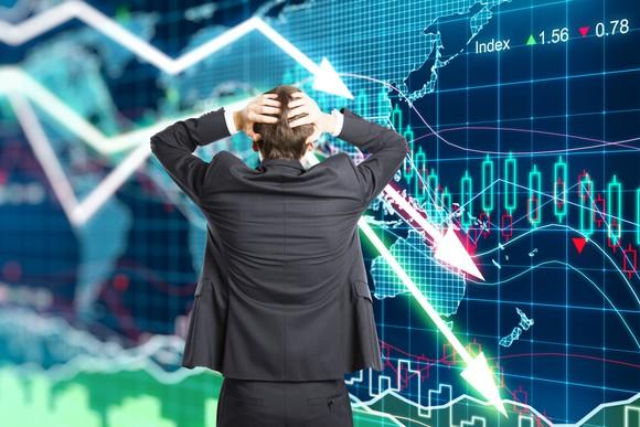 A person in a suit with their hands on the back of their head watching a stock chart go lower.
