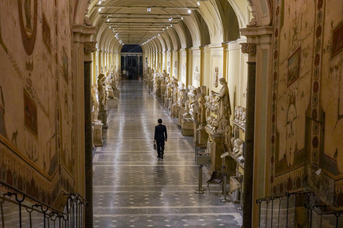 """Gianni Crea, the Vatican Museums chief """"Clavigero"""" key- keeper, walks down an aisle on his way to open the museum's rooms and sections, the Vatican, Monday, Feb. 1, 2021. Crea is the """"clavigero"""" of the Vatican Museums, the chief key-keeper whose job begins each morning at 5 a.m., opening the doors and turning on the lights through 7 kilometers of one of the world's greatest collections of art and antiquities. The Associated Press followed Crea on his rounds the first day the museum reopened to the public, joining him in the underground """"bunker"""" where the 2,797 keys to the Vatican treasures are kept in wall safes overnight. (AP Photo/Andrew Medichini)"""