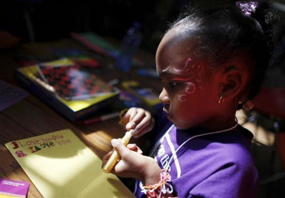 Sunshine, 7, makes a Father's Day card for her father Kinney, who said he was serving life for murder, during a visit to San Quentin state prison in San Quentin, California June 8, 2012.