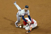 Atlanta Braves second baseman Johan Camargo, left, leaps over Philadelphia Phillies' J.T. Realmuto after forcing him out at second on a double play hit into by Jean Segura during the ninth inning of a baseball game, Sunday, Aug. 30, 2020, in Philadelphia. (AP Photo/Matt Slocum)