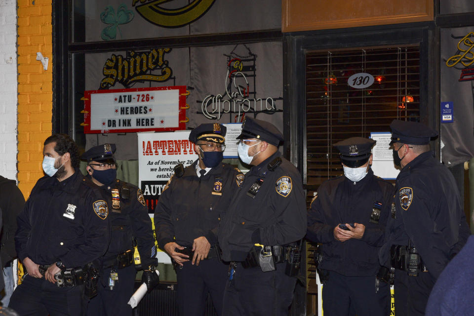 FILE —In this Dec. 1, 2020 file photo, New York City Sheriff's deputies stand outside Mac's Public House after co-owner Danny Presti was arrested, in the Staten Island borough of New York. A crackdown on COVID-19 restriction violators has drawn attention to a sheriff in New York City few knew existed. Sheriff Joseph Fucito has worn the badge for the past six years in a civil-enforcement post that hasn't carried the notoriety of his counterparts with roots in Wild West folklore. (Steve White via AP, File)
