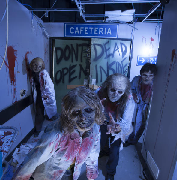 """This image provided by Universal Orlando Resort shows actors portraying zombies at an attraction themed on the AMC show """"The Walking Dead"""" at Universal's Halloween Horror Nights in Orlando, Fla. The theme park also has attractions inspired by the video game and movie """"Silent Hill,"""" Alice Cooper's concept album """"Welcome to My Nightmare"""" and a House of Horrors featuring classic monsters from Universal films. (AP Photo/Universal Orlando Resort, Kevin Kolczynski)"""
