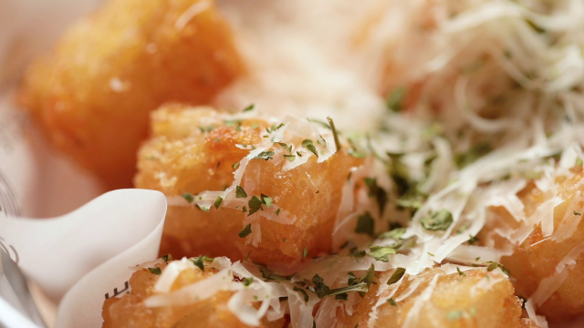 Shaved parmesan cheese on mini golden truffle tater tots