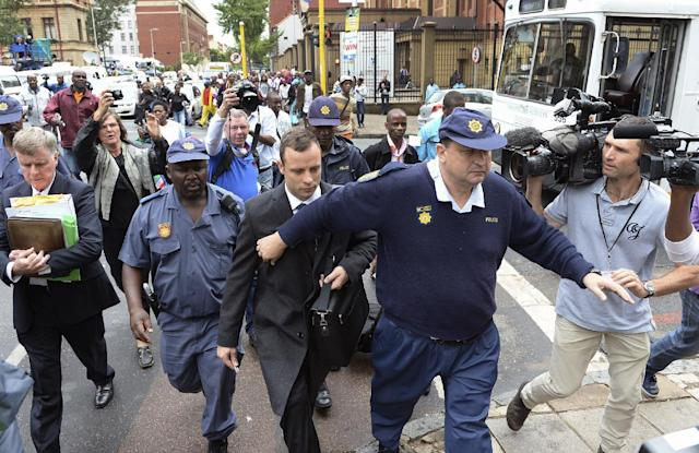 Oscar Pistorius, center, is escorted outside court during a recess on the third day of his trial at the high court in Pretoria, South Africa, Wednesday, March 5, 2014, Pistorius is charged with murder for the shooting death of his girlfriend, Reeva Steenkamp, on Valentines Day in 2013. (AP Photo/Antoine de Ras) SOUTH AFRICA OUT