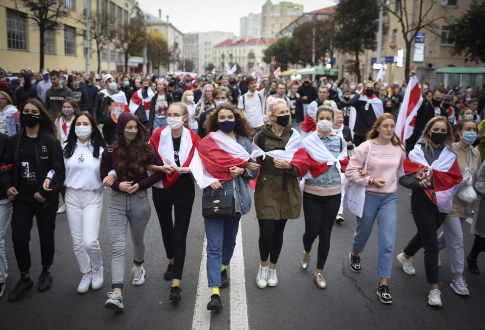 Young people some wearing old Belarusian national flags draped around them, march during an opposition rally to protest the official presidential election results in Minsk, Belarus, Sunday, Sept. 27, 2020. Hundreds of thousands of Belarusians have been protesting daily since the Aug. 9 presidential election. (AP Photo/TUT.by)