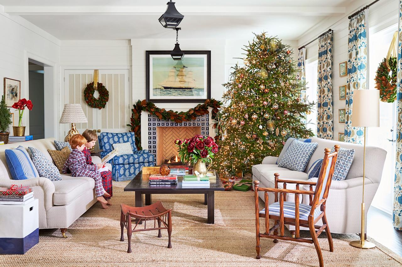 """<p><a href=""""https://www.southernliving.com/home/blue-white-china-pattern-dishes"""">Blue and ivory</a> make up Andrew's signature palette because they're sophisticated on their own and easily accept layers of seasonal hues, like the traditional red and green of the holidays. """"Colors don't clash with each other unless they're very similar and off just a little bit,"""" he says. """"It's not an issue to bring something that's not already there into a room—such as red."""" Peonies picked up from the florist and <a href=""""https://www.southernliving.com/garden/grumpy-gardener/dont-chuck-your-amaryllis"""">potted amaryllis</a> purchased from the <a href=""""http://www.amaryllis.com/"""">Amaryllis & Caladium Bulb Co.</a> provide the rich hit that plays off the metallic ornaments on the tree in the family room. </p>"""