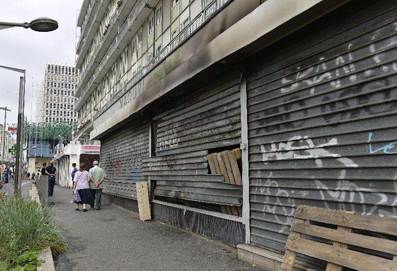 People walk past a damaged shopping center in Sarcelles, on July 21, 2014. Shops in the north Paris suburb were looted when a pro-Palestinian rally descended into violence the previous day (AFP Photo/Miguel Medina)