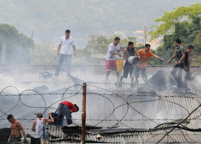 Inmates work to put out a fire on the roof of the penitentiary in San Pedro Sula, Honduras, Thursday March 29, 2012. Honduran authorities say dozens have died at the prison after armed inmates started a fire during a riot. At least 14 people died during the uprising by armed inmates at the prison Thursday, one of them decapitated and the others killed by a fire started by rioters, authorities said. (AP Photo)