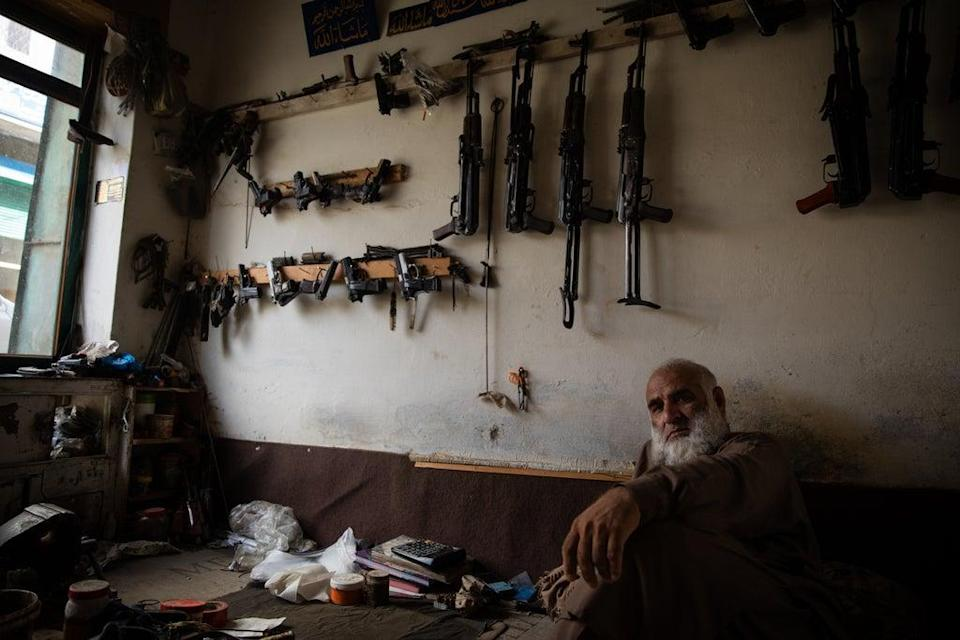 A  50-year-old man sits in his weapon shop near Peshawar, Pakistan. (Oliver Marsden)
