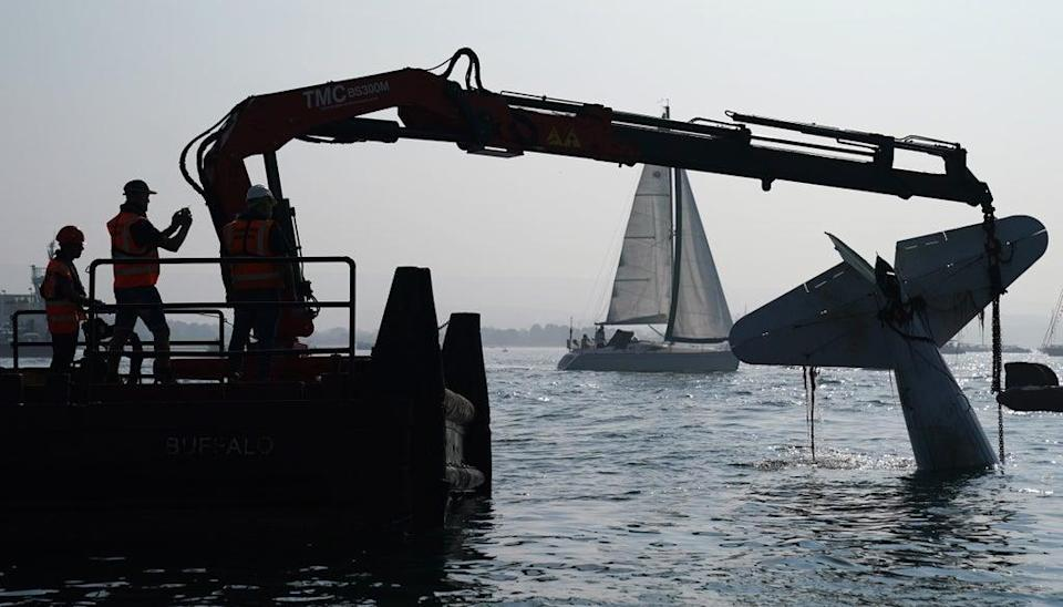 A crane lifts the plane from Poole harbour (Andrew Matthews/PA) (PA Wire)