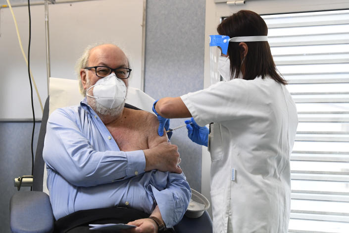 Dr. Massimo Vajani, 67, receives the Pfizer-BioNTech COVID-19 vaccine, at the Civico hospital, in Codogno, the northern Italian town that recorded Italy's first locally spread coronavirus infection, Sunday, Dec. 27, 2020. European Union nations officially kicked off a coordinated effort Sunday to give COVID-19 vaccinations to some of the most vulnerable among their nearly 450 million people, marking a moment of hope in the continent's battle against the worst public health crisis in a century. (Flavio Lo Scalzo/Pool via AP)
