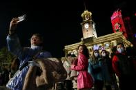 People pose for a selfie as they celebrate the arrival of the new year in Wuhan