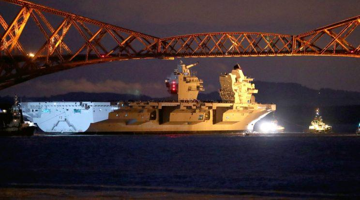 HMS Queen Elizabeth, one of two new aircraft carriers for the Royal Navy, is pulled by tugs under the Forth Rail Bridge in the Firth of Forth on Monday night (PA)