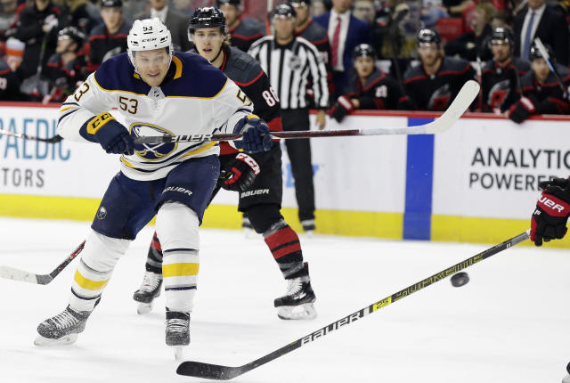 Buffalo Sabres' Jeff Skinner (53) passes the puck while Carolina Hurricanes' Teuvo Teravainen (86), of Finland, chases during the first period of an NHL hockey game in Raleigh, N.C., Saturday, March 16, 2019. (AP Photo/Gerry Broome)