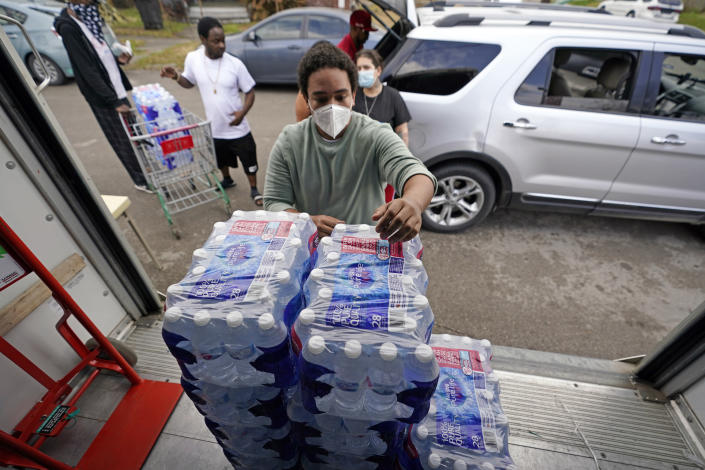 Marcel McClinton hands out cases of donated water to residents affected by a severe winter storm, Friday, Feb. 26, 2021, in Houston. Local officials, including Houston Mayor Sylvester Turner, say they have focused their efforts during the different disasters on helping the underserved and under-resourced but that their work is far from complete. (AP Photo/David J. Phillip)