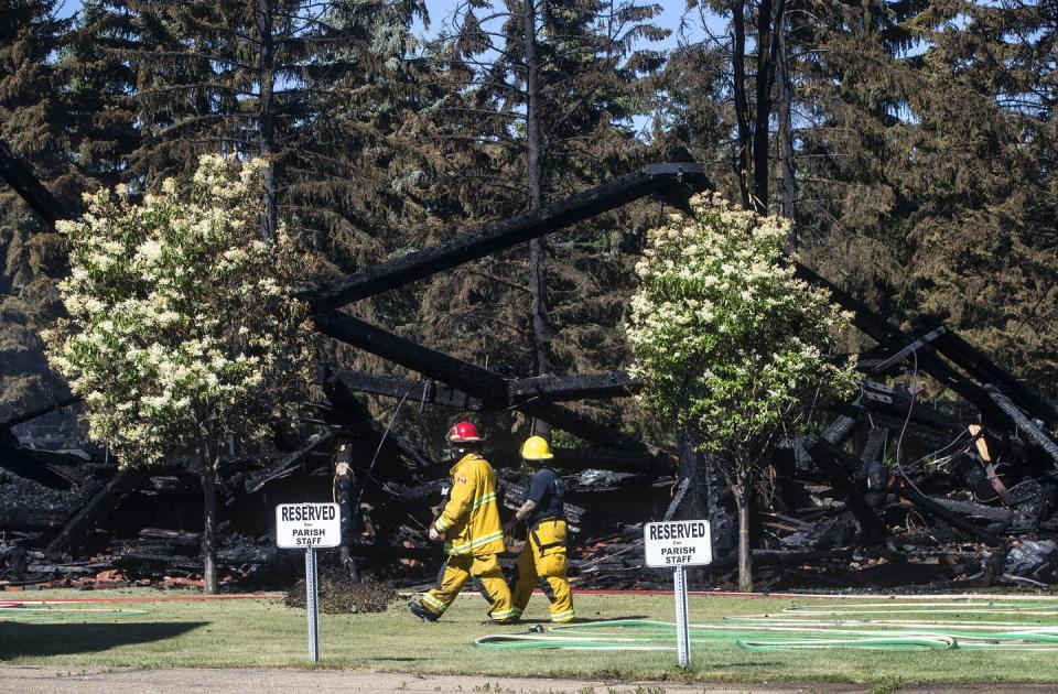 """<span class=""""caption"""">Firefighters walk past the remains of a Catholic church that was on fire, in Morinville, Alta. in June 2021.</span> <span class=""""attribution""""><span class=""""source"""">THE CANADIAN PRESS/Jason Franson</span></span>"""