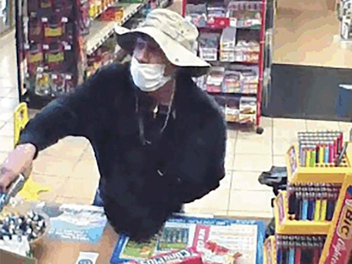 This March 26, 2020 image from surveillance video shows a man wearing a surgical mask holding a gun in a Connecticut convenience store.