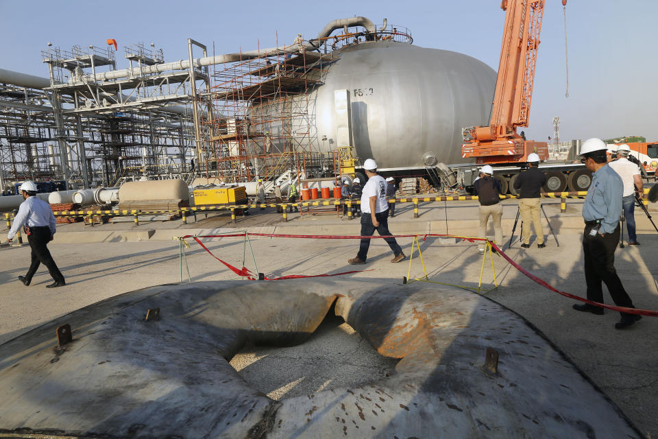 During a trip organized by Saudi information ministry, a hole in a part of a separator is seen on the ground as worker fix the damage in Aramco's oil separator at processing facility after the recent Sept. 14 attack in Abqaiq, near Dammam in the Kingdom's Eastern Province, Friday, Sept. 20, 2019. Saudi Arabia allowed journalists access Friday to the site of a missile-and-drone attack on a facility at the heart of the kingdom's oil industry, an assault that disrupted global energy supplies and further raised tensions between the U.S. and Iran. (AP Photo/Amr Nabil)