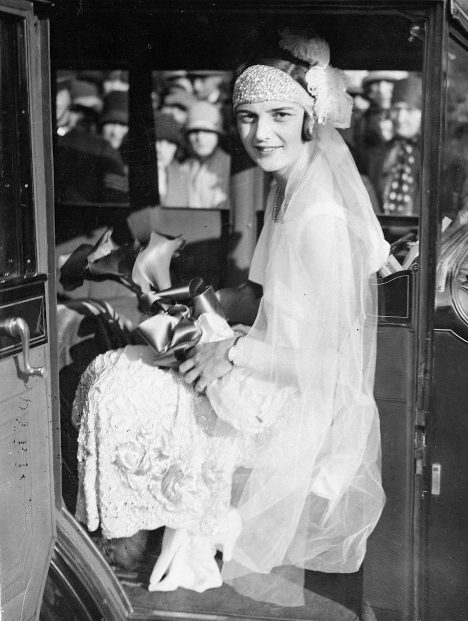 <p>Famed English tennis player Eileen Bennett wed racehorse trainer Marcus Marsh on September 28, 1936. She often wore headbands on the court and chose to walk down the aisle in a headpiece and long veil, which were in fashion at the time. </p>