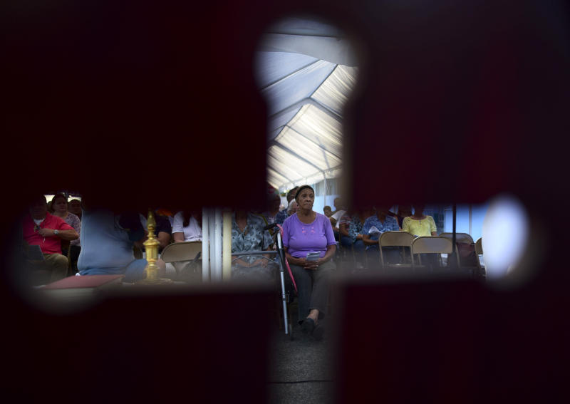 Seen through the cut-out shape of a cross on a priest's chair, a woman attends an outdoor Mass under a tent set up near the Immaculate Concepcion Catholic Church, which sustained earthquake-related damaged earlier in the week, following a magnitude 5.9 quake earlier in the day in Guanica, Puerto Rico, Saturday, Jan. 11, 2020. The morning quake caused further damage along the island's southern coast, where previous recent quakes have toppled homes and schools. (AP Photo/Carlos Giusti)