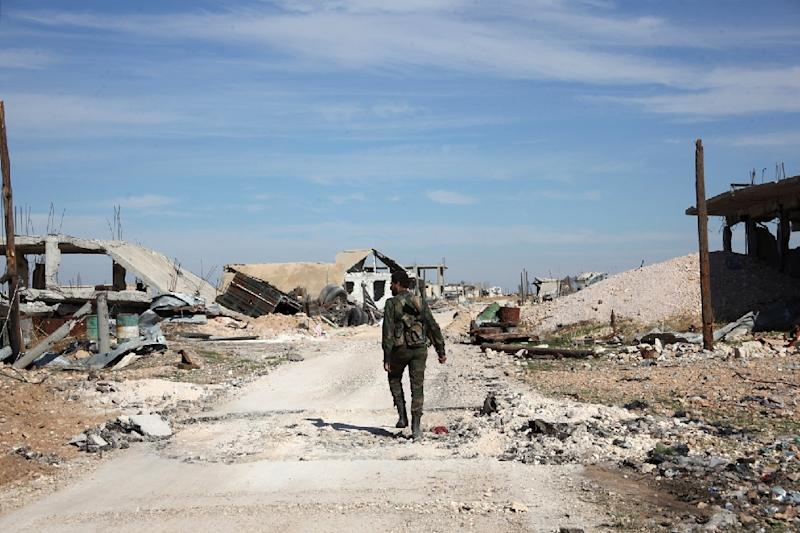 A pro-government fighter walks down a road in the Syrian town of Arbid on the outskirts of Kweyris military airbase, in the northern province of Aleppo, on November 12, 2015 (AFP Photo/George Ourfalian)