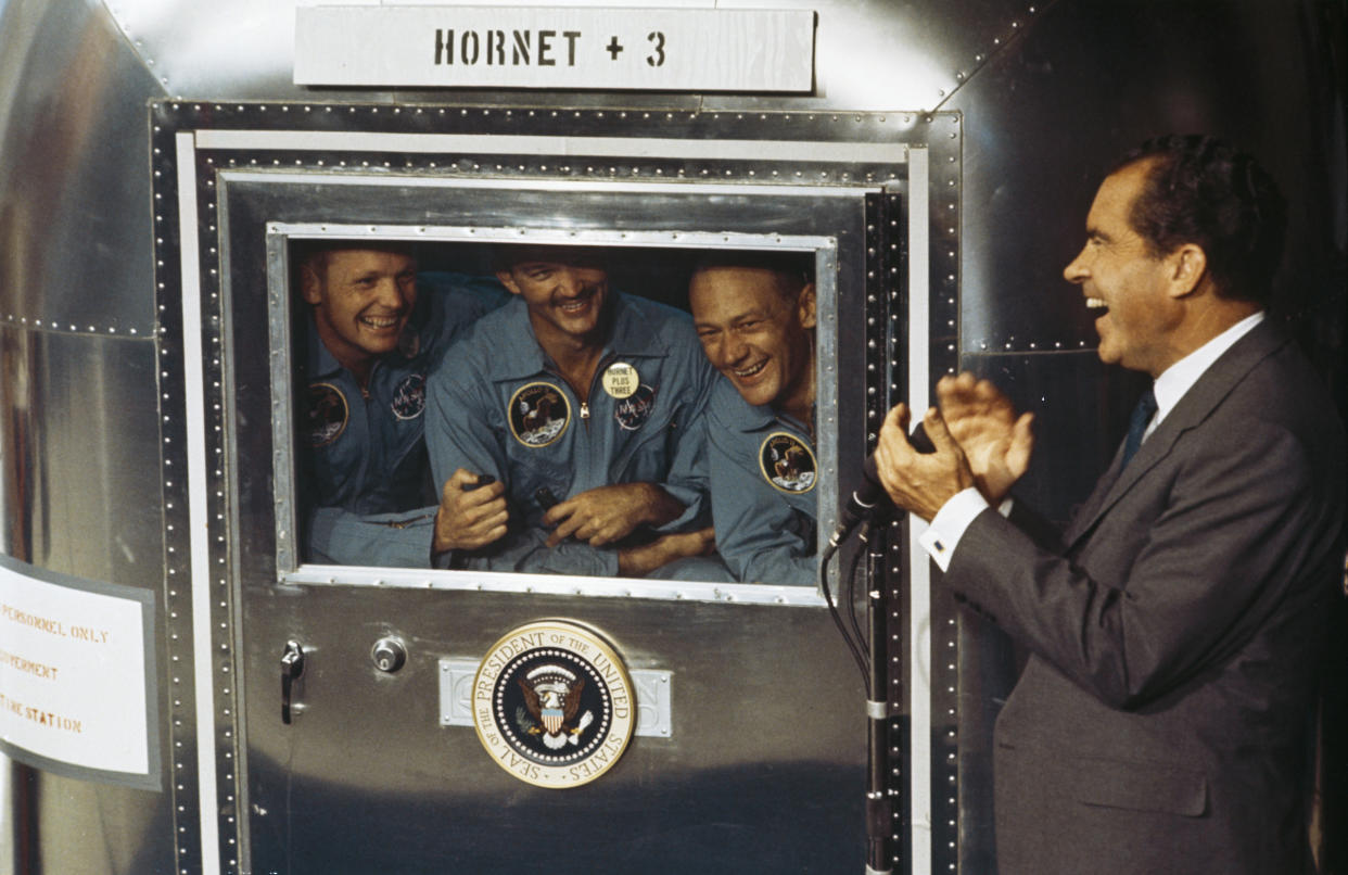From left to right, Neil Armstrong, Michael Collins and Buzz Aldrin, the crew of the historic Apollo 11 moon landing mission, are subjected to a period of quarantine upon their return to earth. Through the window of their Mobile Quarantine Facility, they hold a conversation with President Richard Nixon. | MPI/Getty Images