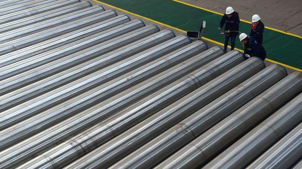 Workers check on seamless steel pipes at a steel factory in Hebei province, China