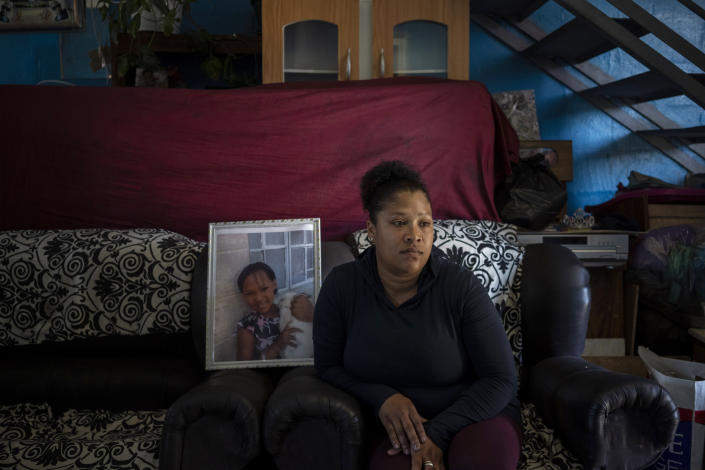 Carmen van Wyk sits on a sofa in her house next to a framed photograph of her daughter, Tazne, in Cape Town, South Africa, on Sept. 10, 2020. The 8-year-old girl was abducted next to her house and her body was found two weeks later next to a highway. She had been raped and murdered. (AP Photo/Bram Janssen)