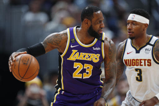 Los Angeles Lakers forward LeBron James, left, works the ball inside as Denver Nuggets forward Torrey Craig defends during the second half of an NBA basketball game Wednesday, Feb. 12, 2020, in Denver. The Lakers won 120-116 in overtime. (AP Photo/David Zalubowski)