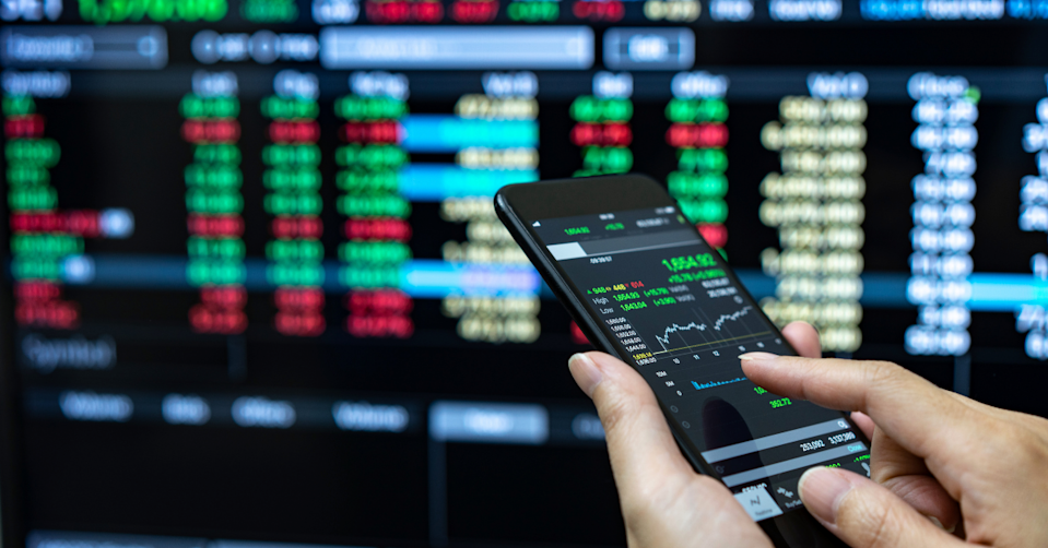 A person looking a stock prices on their phone in front of a screen that is displaying more stock prices.