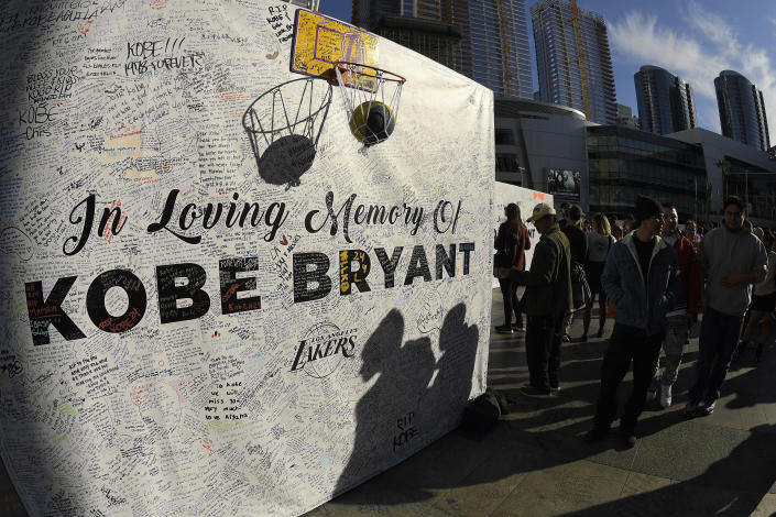 FILE - In this Jan. 28, 2020, file photo, shadows are cast on a memorial wall as fans gather at LA Live, near Staples Center where the Los Angeles Lakers play, to memorialize Kobe Bryant in Los Angeles following a helicopter crash that killed the former NBA basketball player, his 13-year-old daughter, Gianna, and seven others. (AP Photo/Mark J. Terrill, File)