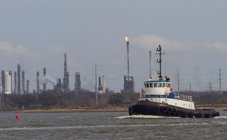 FILE PHOTO: A tug boat navigates the Houston ship channel with a flare from an oil refinery and storage facility in the background south of downtown Houston January 30, 2012.  REUTERS/Richard Carson/File Photo