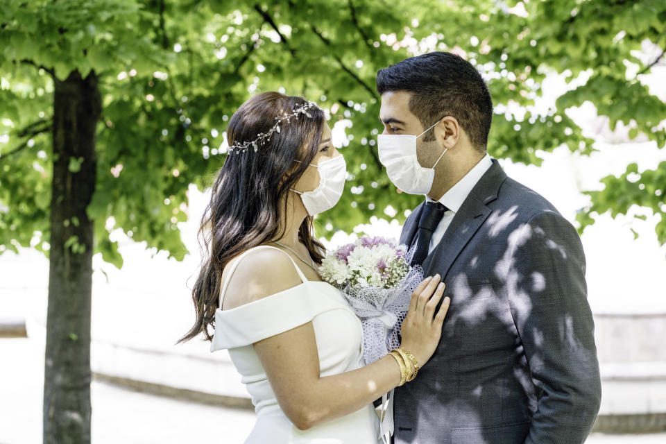 bride and groom in a face protection masks