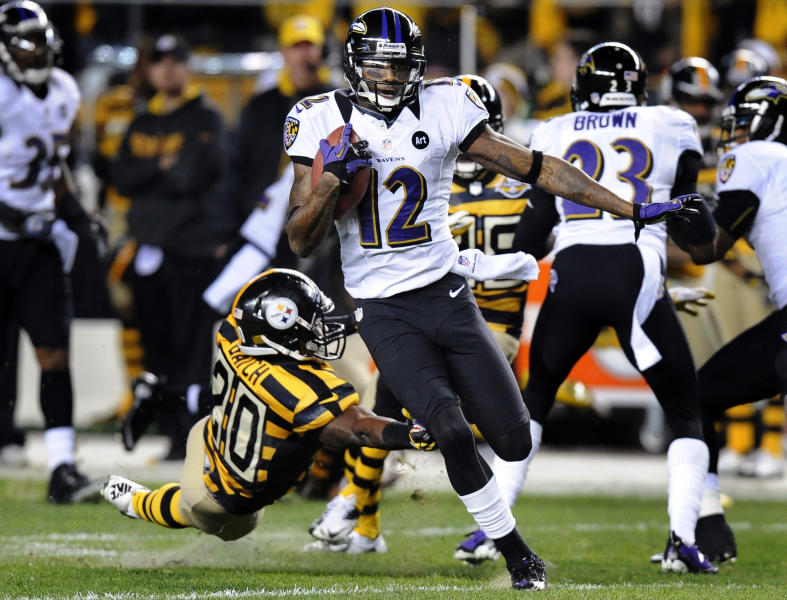 Baltimore Ravens' Jacoby Jones (12) returns a punt past Pittsburgh Steelers' Baron Batch (20) on his way to a touchdown in the first quarter of an NFL football game, Sunday, Nov. 18, 2012, in Pittsburgh. (AP Photo/Don Wright)