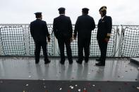 Colleagues of the cabin crew of Sriwijaya Air flight SJ 182, which crashed into the sea, stand on the deck of Indonesia's Naval ship KRI Semarang, as they visit the site of the crash to pay their tribute at the sea off the Jakarta coast